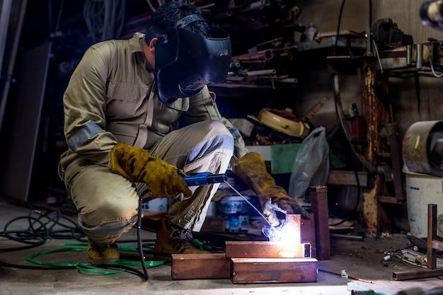 Soldador com uniforme de proteção e máscara de tubo de metal de solda na fábrica.