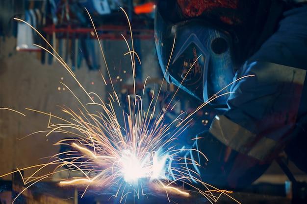 Soldador de solda construção metálica na fábrica.