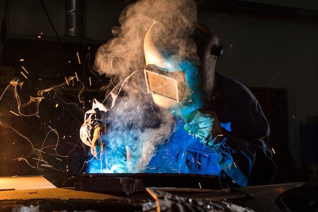 Soldador elétrico trabalhando com solda de argônio, um soldador usando uma máscara enquanto trabalhava em detalhes