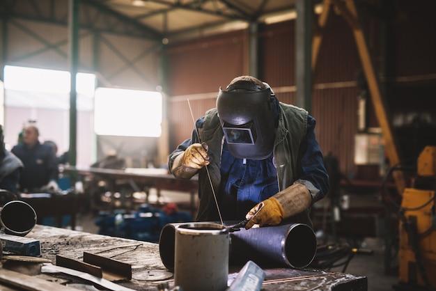 Soldador em uniforme de proteção e máscara de solda de tubo de metal na mesa industrial enquanto faíscas voam