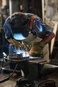 Soldador industrial com máscara protetora trabalhando com tocha que solda metal na oficina