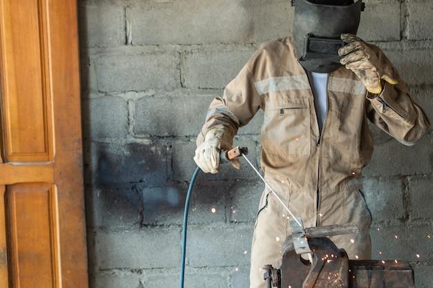Soldador irreconhecível usando capacete de proteção especial soldando detalhes de metal usando uma tocha