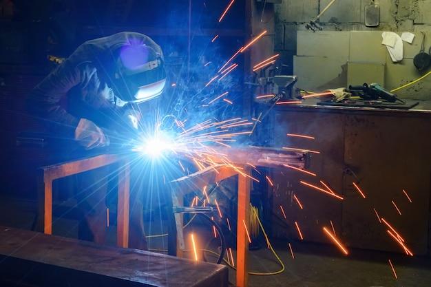 Soldador junta peças de metal. um processo de soldagem semiautomática.