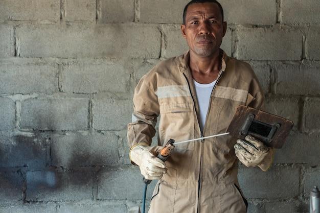 Soldador latino durante um dia de trabalho na fábrica metalúrgica.