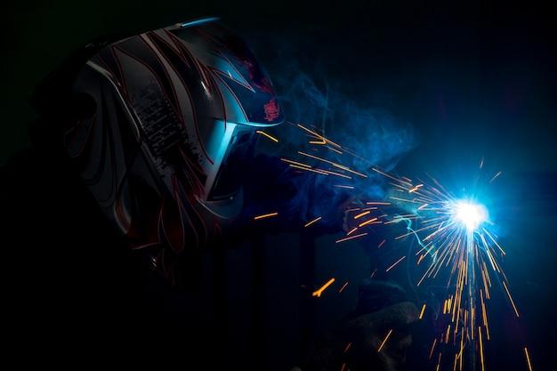 Soldador masculino em uma máscara que executa a soldadura do metal. foto em cores escuras. faíscas voando.