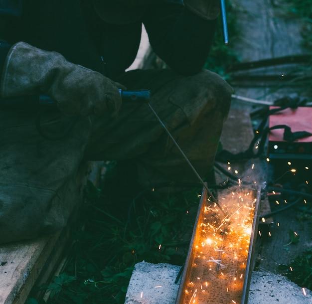 Soldador masculino trabalhando queima buraco eletrodo no canal de aço à noite