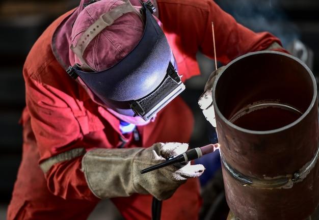 Soldador na fábrica com tubo de solda de equipamentos de proteção
