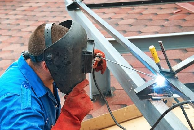 Soldador na fábrica trabalhando com construção metálica