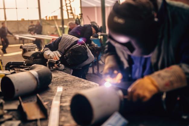 Soldador profissional em uniforme de proteção e máscara de soldagem de tubo de metal na oficina.