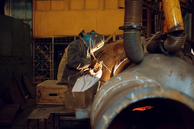 Soldador trabalha com metal na fábrica, habilidade de soldagem