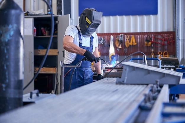 Soldador usando macacão de trabalho e capacete de proteção enquanto usa a tocha de soldagem na estação de serviço automotiva
