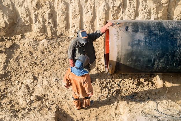 Soldadores profissionais trabalhando na construção de gasodutos.