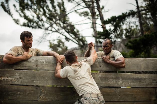 Soldados ajudando homem a escalar parede de madeira