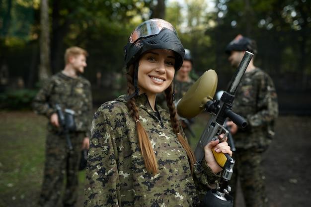 Soldados camuflados e máscaras jogando paintball, guerra no playground na floresta. esporte radical com arma pneumática e balas ou marcadores de tinta, jogo de equipe militar ao ar livre, táticas de combate