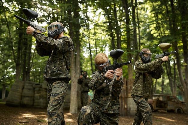 Soldados camuflados e máscaras jogando paintball na floresta. esporte radical com arma pneumática e balas ou marcadores de tinta, jogo de equipe militar ao ar livre, táticas de combate