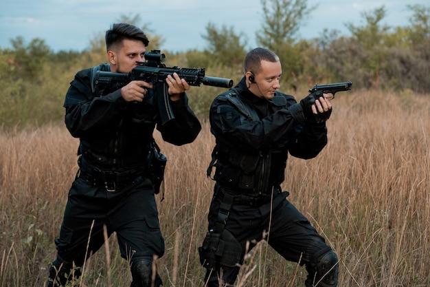 Soldados das forças especiais em uniforme preto com armas