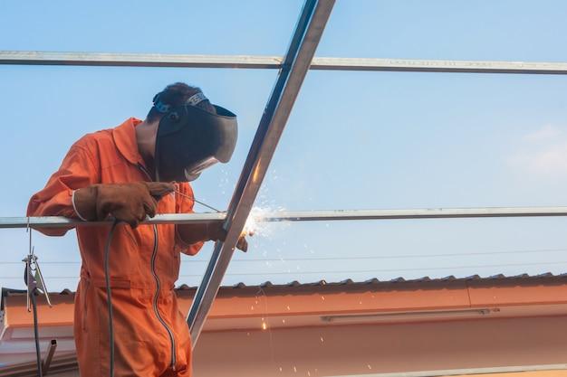 Soldadura de trabalhador na roupa de trabalho alaranjada que solda para a treliça do telhado