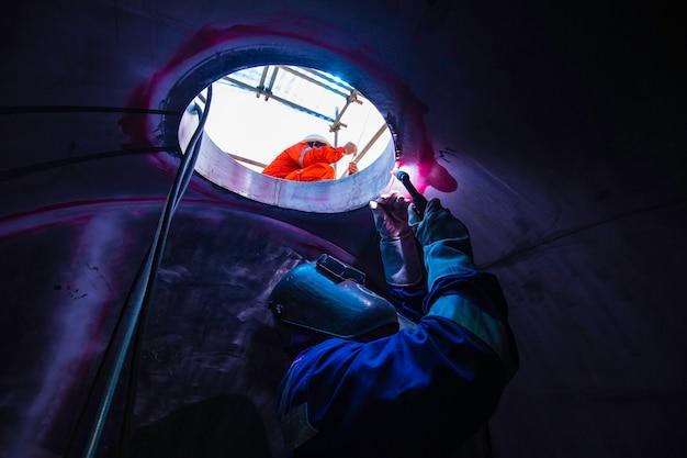 Soldagem arc argônio trabalhador masculino metal reparado é soldagem faíscas construção industrial tanque parte bueiro óleo inoxidável dentro de espaços confinados há um vigia fora.