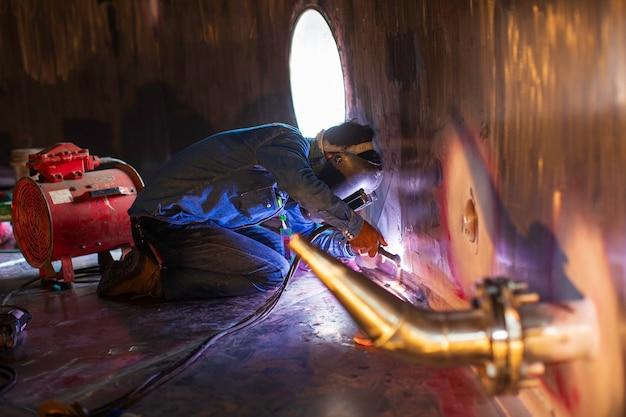 Soldagem arco argônio trabalhador masculino metal reparado está soldando faíscas tanque de construção industrial de óleo inoxidável dentro de espaços confinados.