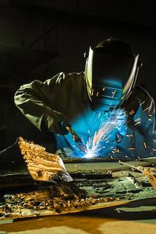 Soldagem com argônio, um soldador usando uma máscara enquanto trabalha nos detalhes