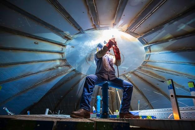Soldagem de arco de metal de trabalhador masculino é parte da construção do tanque do telhado, óleo de petróleo e tanque de armazenamento de gás dentro de espaços confinados.