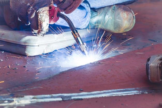 Soldagem de gás inerte de metal de trabalho de close-up (mig) ou aços de carbono de placa de metal soldando à estrutura. o processo pode ser semiautomático ou automático.