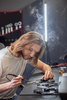 Soldagem, microcircuito. jovem homem de cabelos compridos interessado em uma camiseta clara tocando o microcircuito com o ferro de solda sentado à mesa de trabalho
