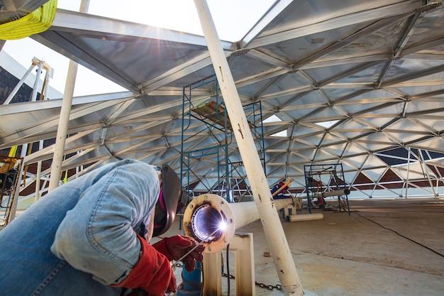 Soldar o metal do trabalhador masculino faz parte do espaço confinado de alumínio da cúpula do tanque de armazenamento da tubulação do bico da maquinaria.