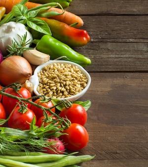 Soletrado em uma tigela e legumes frescos em uma mesa de madeira