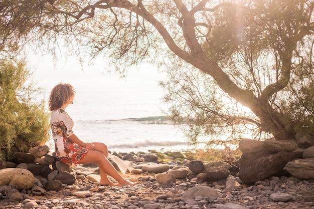 Solitária, doce, linda, jovem, de meia-idade, sentada na costa em uma rocha perto do oceano