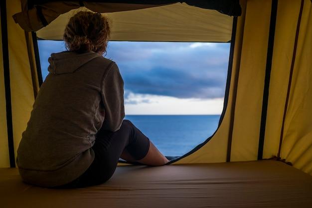 Solitária, independente, forte, mulher de meia-idade sentindo a natureza ao ar livre em uma barraca de teto no carro