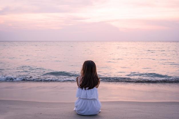 Solitária jovem mulher asiática, sentado na praia ao pôr do sol