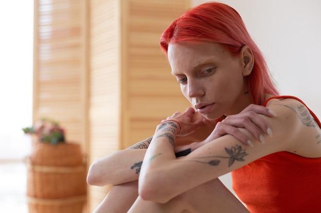 Solitário e triste. jovem ruiva anoréxica com tatuagens se sentindo extremamente solitária e triste