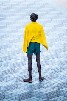 Solitário homem africano negro, em paz com uma toalha depois de sair da praia em um ambiente urbano