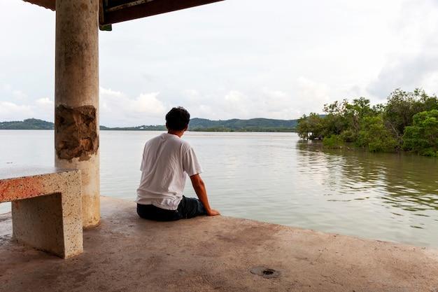 Solitário homem asiático sentado sozinho em um píer em dia de mau tempo