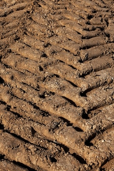 Solo bem arado no campo agrícola antes do plantio das plantas, close-up de vestígios de trator deixados no solo