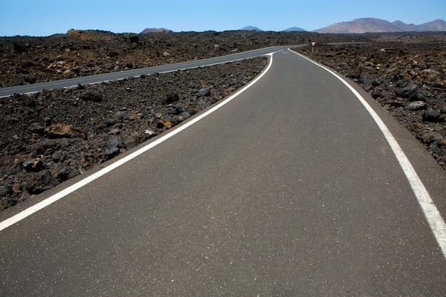 Solo vulcânico preto e detalhe da estrada em lanzarote