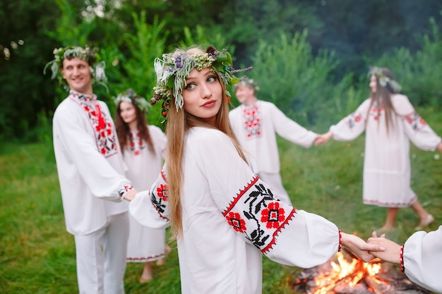 Solstício de verão. jovens em roupas eslavas giram em torno de um incêndio no solstício de verão. .