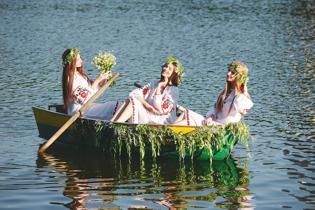 Solstício de verão. moças em trajes nacionais navegam em um barco decorado com folhas e crescimentos. férias eslavas de ivan kupala.