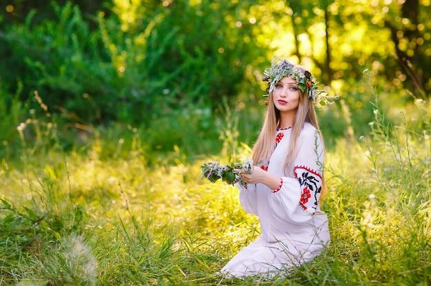 Solstício de verão. mulher tecendo uma coroa de flores perto do fogo.