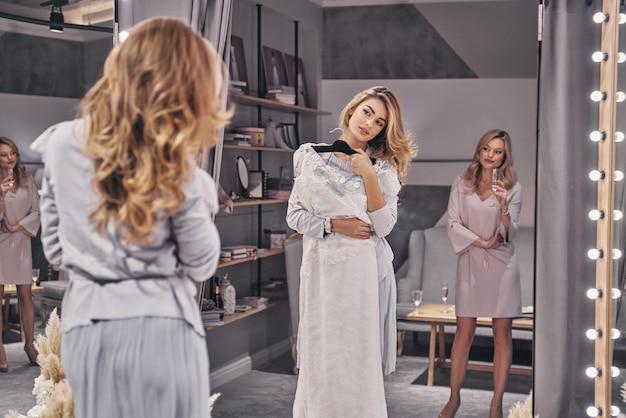 Solte sua imaginação? mulheres jovens e atraentes experimentando um vestido de noiva enquanto passam um tempo na loja de noivas com a namorada