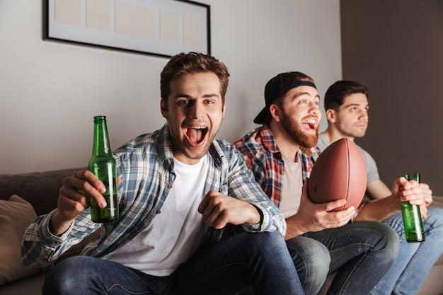 Solteiros masculinos e alegres gritando enquanto festejam em casa e assistindo futebol jogar com cerveja