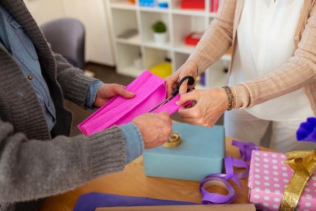 Soluções criativas. close de um papel de embrulho sendo cortado enquanto decorava as caixas de presente