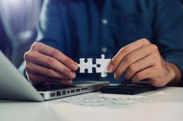 Soluções de negócios e conceito de sucesso. mão de empresário conectando o quebra-cabeça no escritório à luz da manhã
