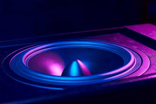 Som alto-falante com luzes de neon em fundo escuro. monitor dinâmico closeup. backgroound criativo