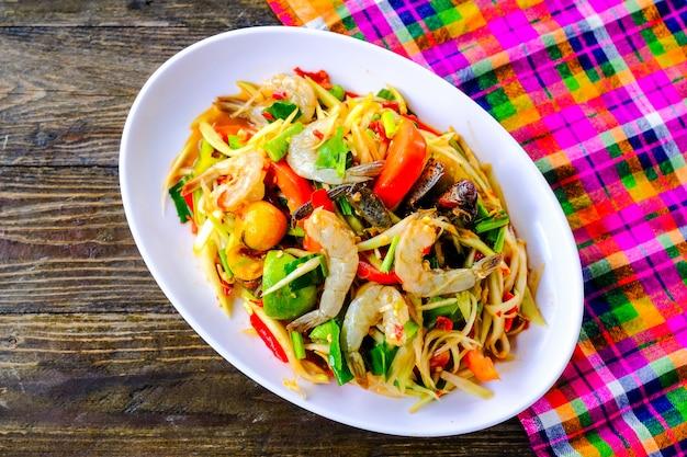 Som tam frutos do mar (salada de papaia picante) com caranguejo salgado, na mesa de madeira (comida tailandesa)