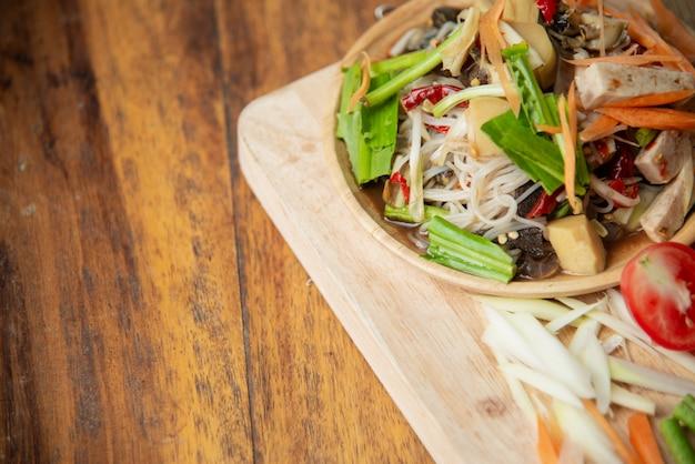 Som tam tailandês, salada de papaia tailandês em fundo de madeira