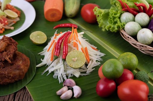 Som tam thai - estilo tailandês do alimento da salada da papaia dos ingredientes na tabela de madeira. conceito de comida tailandesa.