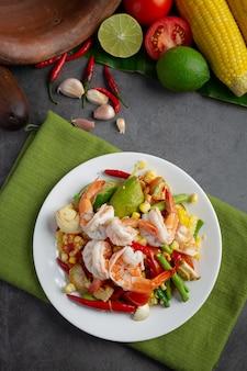Som tum com milho e camarão, servido com macarrão de arroz e salada verde. decorado com ingredientes da comida tailandesa.