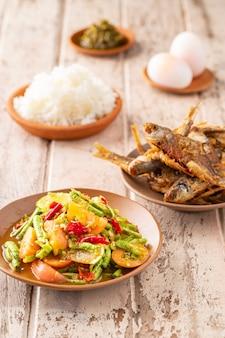 Som tum tua, tam toua, comida tailandesa, salada de feijão comprido picante com peixe frito crocante, arroz no vapor, ovos cozidos e molho picante em um fundo de textura de madeira branca